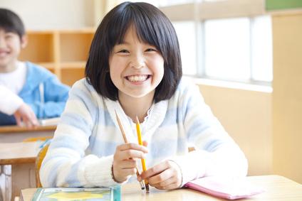 席に座って微笑む小学生女子